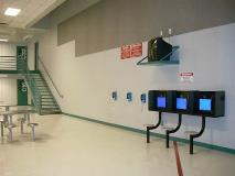 Dayrooms are large common areas where the inmates can watch T.V., play card or board games, talk on the telephones or have a visit on one of the visiting monitors.